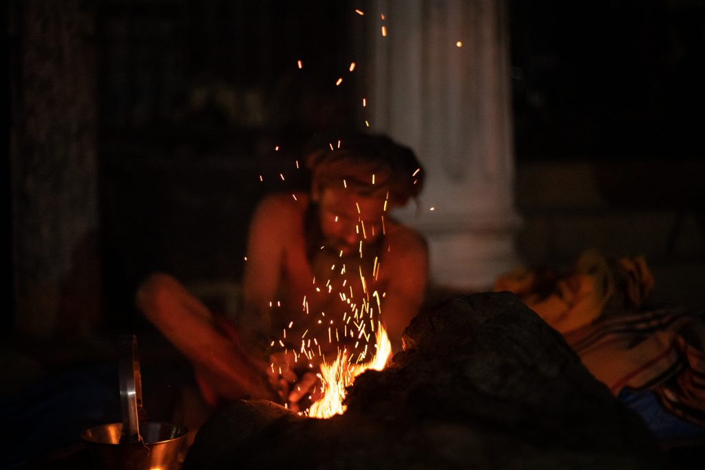 A sadhu warms himself by sitting nearby the fire at Pashupatinath Temple, Nepal