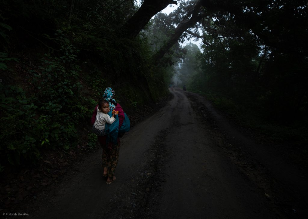A woman carries her baby on her back, in a traditional manner at Timal.